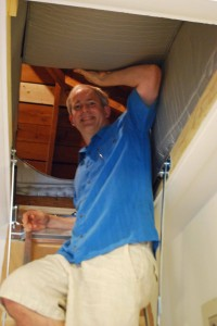 Rich Layman shows off his insulated attic hatch at the house party
