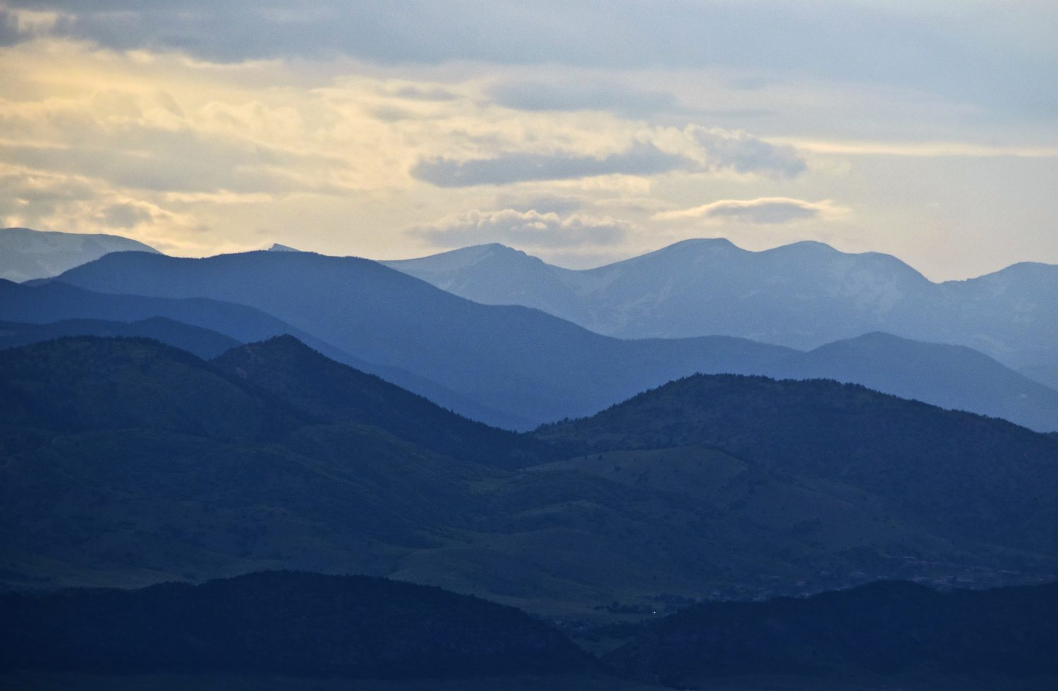 The ridges of the Rocky Mountains are layers of blue silhouettes when backlit by the evening sun